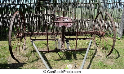 harrow tool fence sky - old corroded rusty harrowing field...