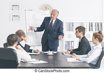 Senior businessman criticising a young employee in front of other members of a corporate meeting