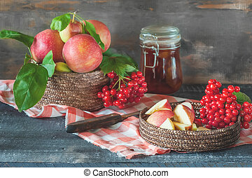 Harvest apples and viburnum in a basket prepared for cooking jam on the table in the fall. The concept of home harvesting and healthy eating. Rustic style.