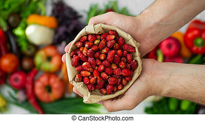 Harvest, Autumn. Fresh healthy fruits and vegetables. Healthy eating background. Red Strawberries in the hands of men closeup