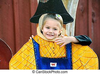 Harvest Festival Scarecrow - Little girl peaks her head...