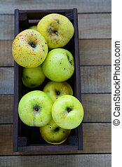 harvest of green apples in wooden crate