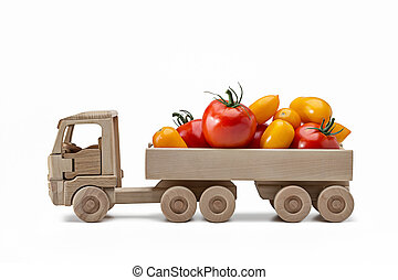 Bouquet of ripe tomatoes in trailer, toy made of wood. White background, studio shot, close-up.