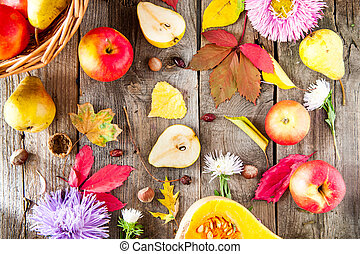 Harvest or Thanksgiving background with autumnal fruits, flowers, leaves, pumpkin, nuts and berries on the rustic wooden table. Autumn concept background. Selective focus, Top view.