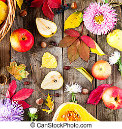 Harvest or Thanksgiving background with autumnal fruits, flowers, leaves, pumpkin, nuts and berries on the rustic wooden table. Autumn concept background. Selective focus, square. Top view.