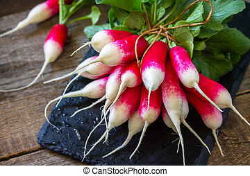 Harvest organics red radish. Organic vegetables. Fresh Radishes on wooden background.