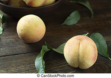 peaches with leaves on the table