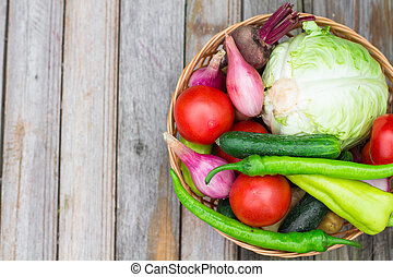 Harvest time. A basket of vegetables on a wooden table