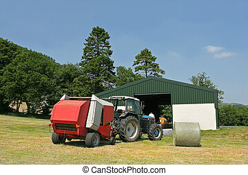Harvest Time - Tractor and hay baler standing in a field in ...