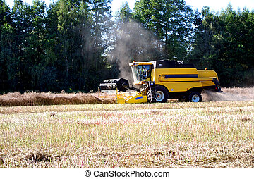harvester on field cutting flax with wood in background