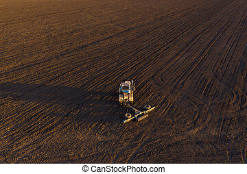 Harvester working in the field at spring and plowing the ...