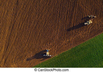 Harvesters working in the field at spring and plowing the ...