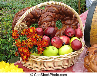 Harvesting apples, bread and flowers in a wooden basket