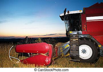 harvesting combine at sunset