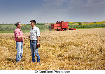 Harvesting - Peasant and businessman shaking hands on wheat...