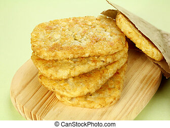 Stack of fried hash browns on a board ready to serve.