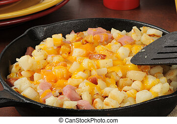 Hash browns with ham and cheese - A cast iron skillet with...