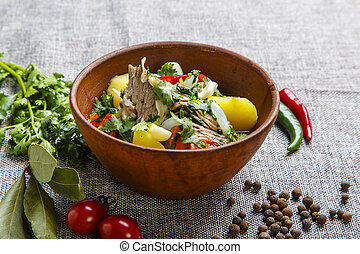 Hashlama in a clay plate. Ingredients: Beef ribs, potatoes, herbs, garlic. The plate stands on a textured gray canvas. Around lie pepper red and green pods, pepper peas, tomatoes, Bay leaf, parsley