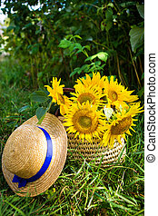 Hat, a bouquet of sunflowers lies in a straw bag on the green grass.