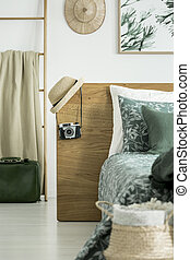 Hat and camera on headboard and blanket on ladder in bedroom...