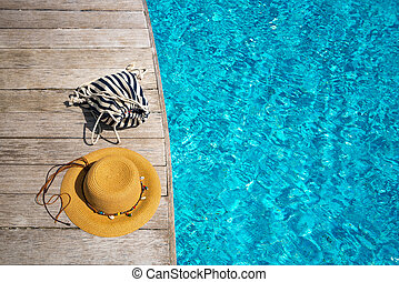 Hat at the side of swimming pool, summer travel concept