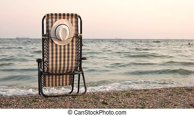 Hat attached to chaise lounge chair on beach. Seashore and...