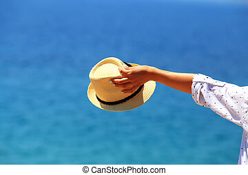 Hat in woman hand on blue sea background
