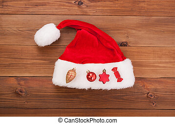 Hat of Santa Claus with Christmas toys on a wooden background.