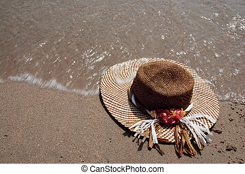 Hat on a beach - Straw hat laying on the beach is washed by...