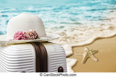 Hat on luggage at the beach
