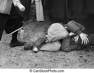 A defenseless homeless man being beaten with a bat. Black and white and film grain effects added for drama.