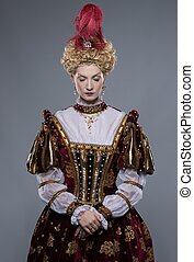 Haughty queen in royal dress isolated on grey