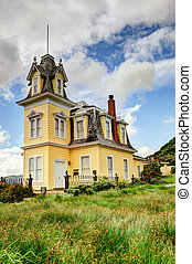 Haunted house by a large grassy field - Yellow three story ...