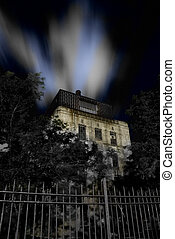 Haunted House - Haunted house with fence and dramatic night...