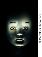 Haunting child's doll face emerging from a dark, shadowy background.