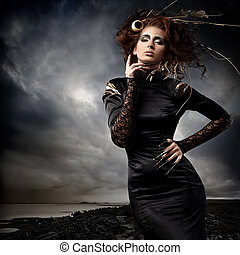 High fashion model in black dress, with long nails and creative hairstyling and makeup in stormy weather