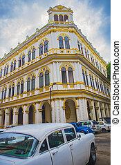 HAVANA, CUBA - DEC 4, 2015: Urban scene with colorful colonial buildings and vintage american car parked in Old Havana street
