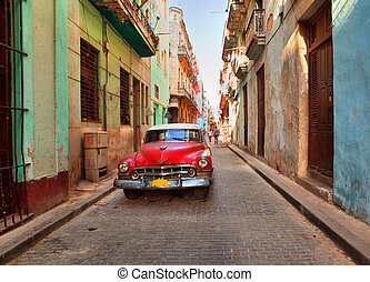 HAVANA, CUBA-MAY 14: Street scene with an old rusty american car on May 14, 2013 in Havana. These classic vintage cars that can be seen all over the country have become a worldwide known symbol of Cuba
