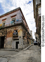 Corner with eroded building facade against blue sky in San ignacio street, Havana, cuba