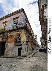 Corner with eroded building facade against blue sky in San ignacio street, Havana, cuba