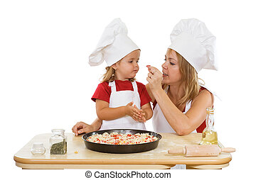 Woman and little girl preparing a pizza - tasting ingredients - isolated