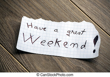 Have a great Weekend - Hand writing text on a piece of paper on wood background
