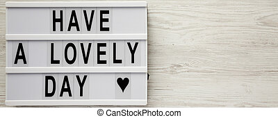 'Have a lovely day' words on lightbox over white wooden background, top view. From above, flat lay, overhead. Copy space.