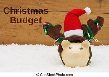 Having a Christmas Budget, Piggy bank with Christmas hat on snow with a weathered wood background with text Christmas Budget