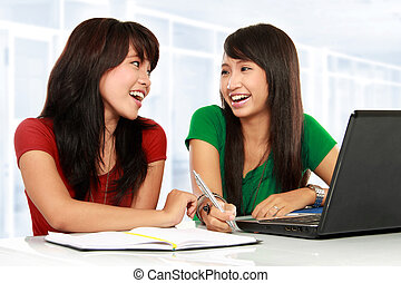 having a conversation - portrait of two young asian student...