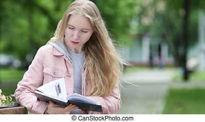 Having a good read - Young beautiful blonde girl in a park ...