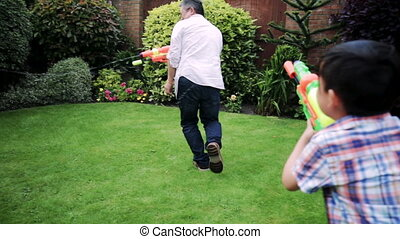 Having a Water Fight with Dad - Family are having a...