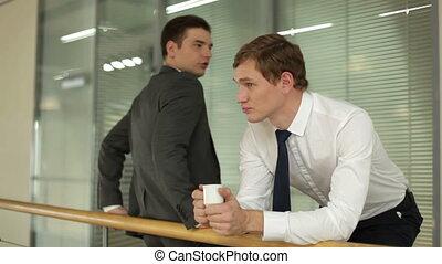 Having break - Two businessmen speaking during coffee break...