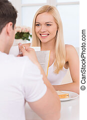 Having breakfast together. Young loving couple having breakfast together