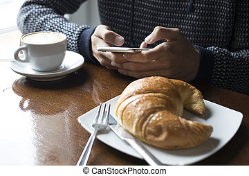 having breakfast with the cellphone in the cafeteria